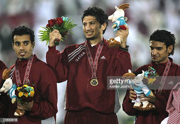 Qatar's Wesam Rizik Abdulmajid celebrates his gold medal with teammates at the awards ceremony for the men's football final between Iraq and Qatar at...
