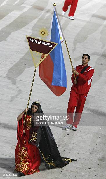 Rafael Nepomuceno carries the country's flag as he leads members of the Philippines delegation as they parade at the opening ceremony for the 15th...