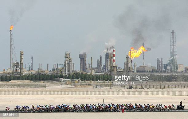 The pack rides past an oil refinery during the third stage of the 5th edition of the Tour of Qatar cycling race between Khalifa stadium and Al Khor...