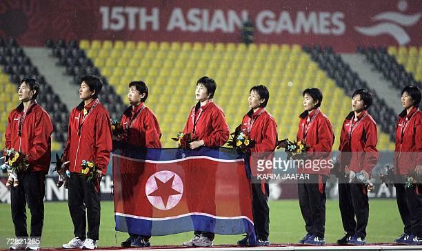 TO GO WITH STORY Asiad2006FblwomenPRKJPN North Korean goalkeeper Jon Myong Hui joins her teammates on the winner's podium after their victory over...
