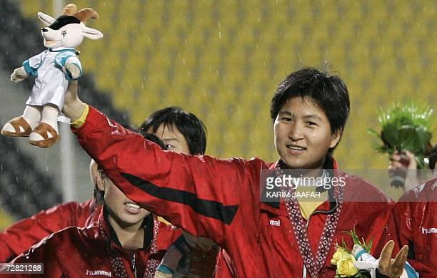 TO GO WITH STORY Asiad2006FblwomenPRKJPN North Korean goalkeeper Jon Myong Hui joins her teammates as they do a lap around the stadium to celebrate...