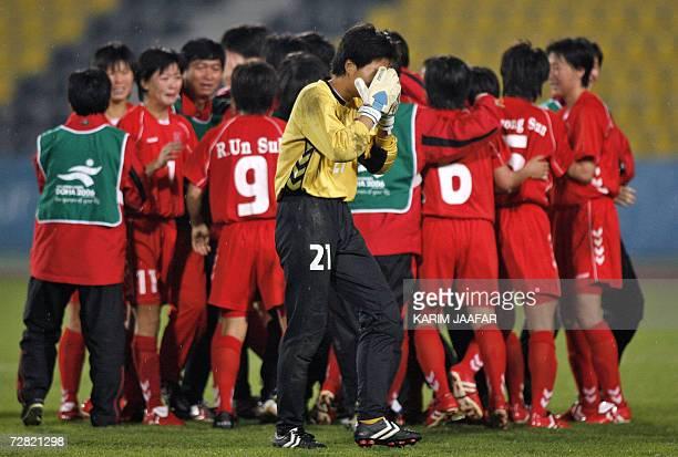 TO GO WITH STORY Asiad2006FblwomenPRKJPN North Korean goalkeeper Jon Myong Hui is overcome with joy as her teammates celebrate their win over Japan...