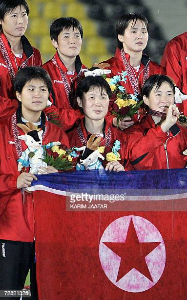 TO GO WITH STORY Asiad2006FblwomenPRKJPN North Korean goalkeeper Jon Myong Hui poses with teammates after their victory over Japan in the women's...