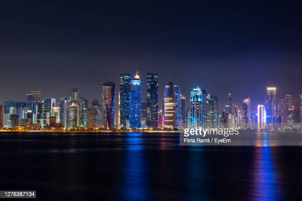 doha skyline lluminated at night - qatar stock pictures, royalty-free photos & images