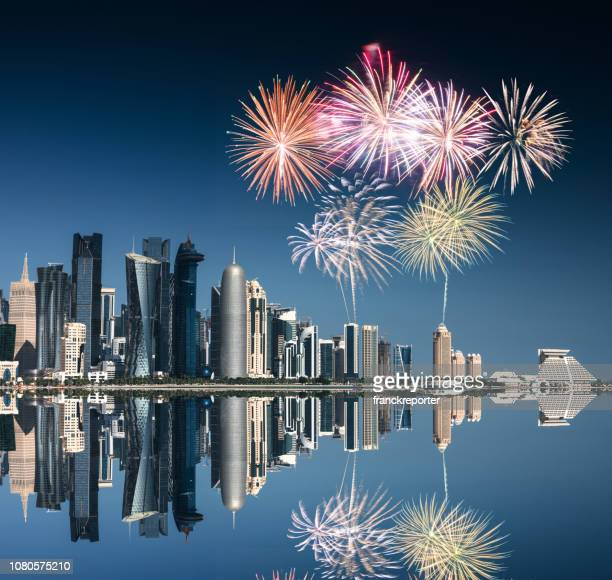 doha skyline reflections with fireworks for the new year - qatar stock pictures, royalty-free photos & images