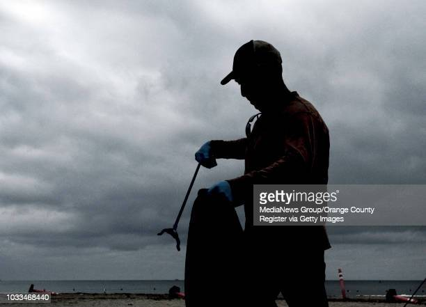 Doheny Longboard Surfing Association volunteer Myron Pines cleans the beach in Dana Point early Tuesday morning. ///ADDITIONAL INFO: - Photo by MINDY...