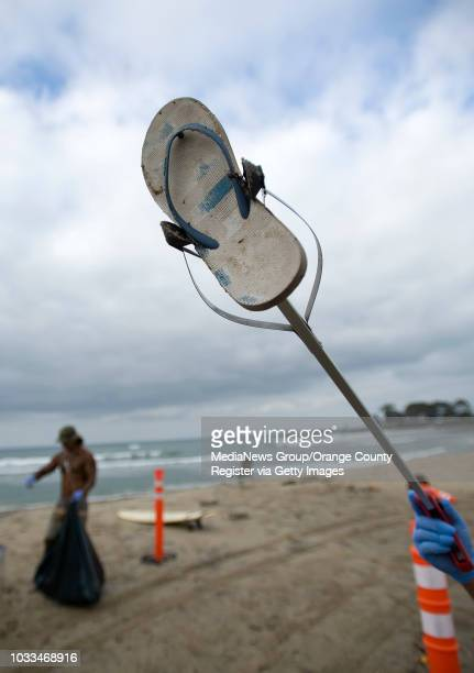Doheny Longboard Surfing Association volunteer Robert Anderson offers up a left flip flop while cleaning the beach after the Fourth of July holiday....