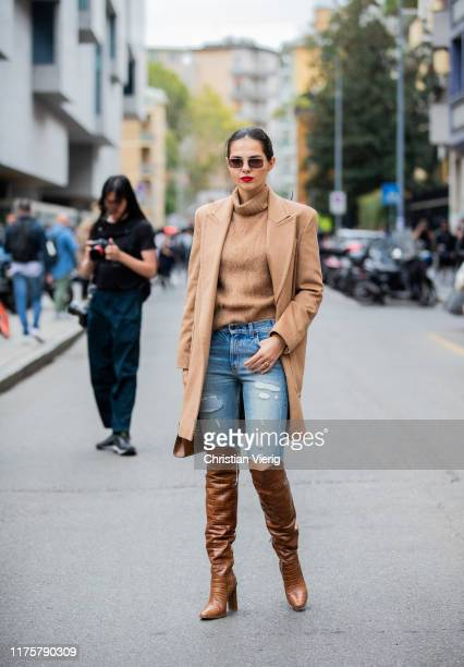 Doina Ciobanu is seen wearing brown boots ripped denim jeans beige coat turtleneck outside the Max Mara show during Milan Fashion Week Spring/Summer...