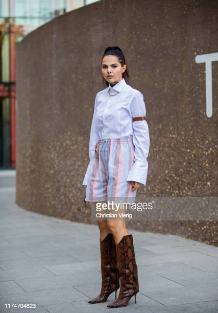Doina Ciobanu is seen wearing striped pastel shorts, white button shirt, sunglasses, boots with snake print outside Ports 1961 during London Fashion...