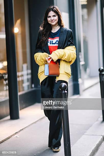 Doina Ciobanu is wearing a yellow bomber jacket a black suit a Fila tshirt outside the Paul Smith show during Paris Fashion Week Menswear Fall/Winter...