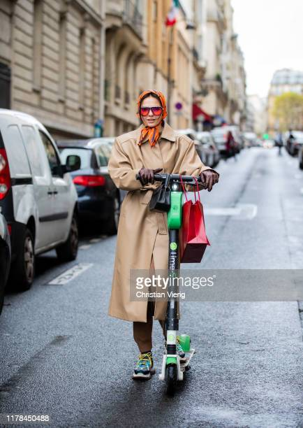 Doina Ciobanu seen riding on a Lime e scooter with shopping bag wearing glovehead scarf, brown trench coat outside Miu Miu during Paris Fashion Week...