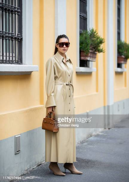 Doina Ciobanu seen wearing beige belted button up dress, brown bag outside Boss during Milan Fashion Week Spring/Summer 2020 on September 22, 2019 in...