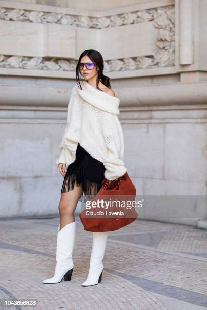 Doina Ciobanu wearing a oversize nude jumper black fringed skirt white boots and tan bag is seen before the Poiret show on September 30 2018 in Paris...