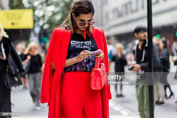 Doina Ciobanu wearing a red coat and pants bag and heels and band tshirt and scarf outside Erdem during London Fashion Week Spring/Summer collections...