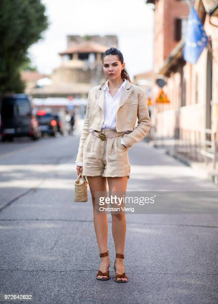 Doina Ciobanu wearing beige shorts jacket straw bag is seen during the 94th Pitti Immagine Uomo on June 12 2018 in Florence Italy