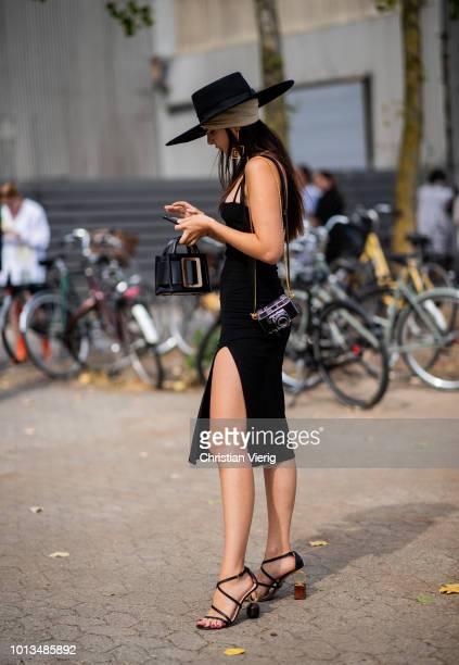 Doina Ciobanu wearing black dress with slit black hat is seen outside Holzweiler during the Copenhagen Fashion Week Spring/Summer 2019 on August 8...