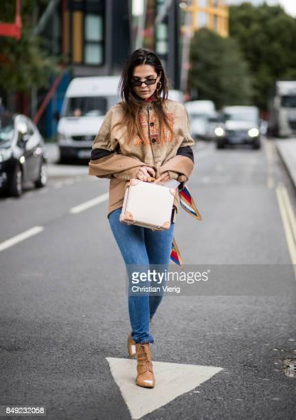 Doina Ciobanu wearing brown top denim jeans ankle boots outside Christopher Kane during London Fashion Week September 2017 on September 18 2017 in...