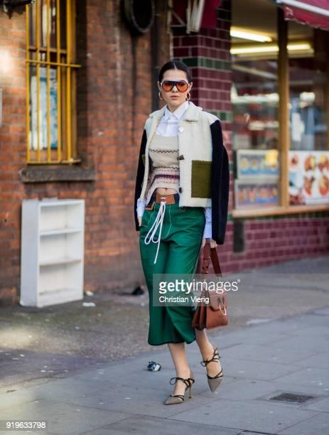 Doina Ciobanu wearing green cropped pants heels brown JW Anderson bag jacket seen outside JW Anderson during London Fashion Week February 2018 on...