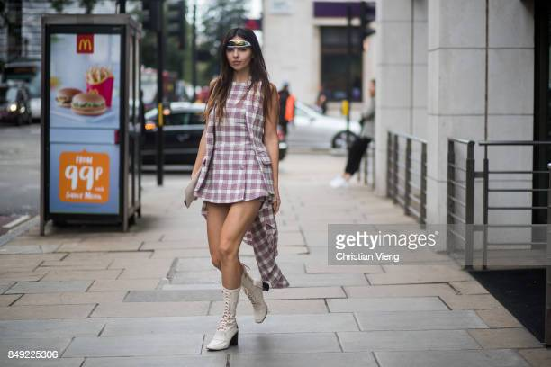 Doina Ciobanu wearing space sunglasses checked dress white ankle boots outside Erdem during London Fashion Week September 2017 on September 18 2017...