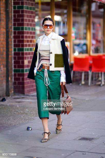 Doina Ciobanu wears a JW anderson brown bag green flare cropped pants a pull over a white shirt shoes sunglasses during London Fashion Week February...