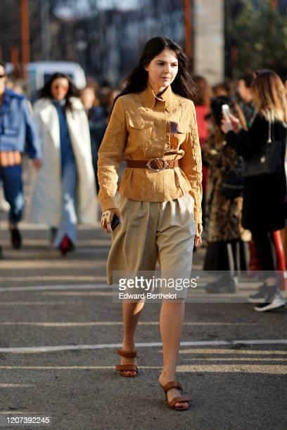 Doina Ciobanu wears a light brown shirt, a belt with metallic buckle, a beige skirt, sandals, outside Alberta Ferretti, during Milan Fashion Week...