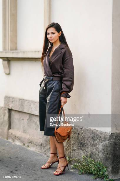 Doina Ciobanu wears a necklace, a lustrous dark brown wrap-over and drop-shoulder long sleeves shirt, a dark brown belt, black leather short pants, a...
