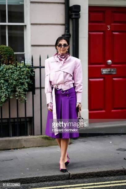 Doina Ciobanu wears a pink jacket a glitter pink turtleneck a purple pleated skirt shoes during London Fashion Week February 2018 on February 16 2018...