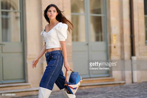 Doina Ciobanu wears a ruffle white top cropped jeans a colored bag yellow heels shoes outside Alexis Mabille during Paris Fashion Week Haute Couture...