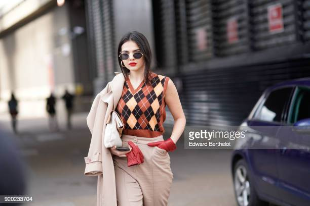 Doina Ciobanu wears a trench coat beige pants red gloves sunglasses a sleeveless pull over red shoes during London Fashion Week February 2018 on...