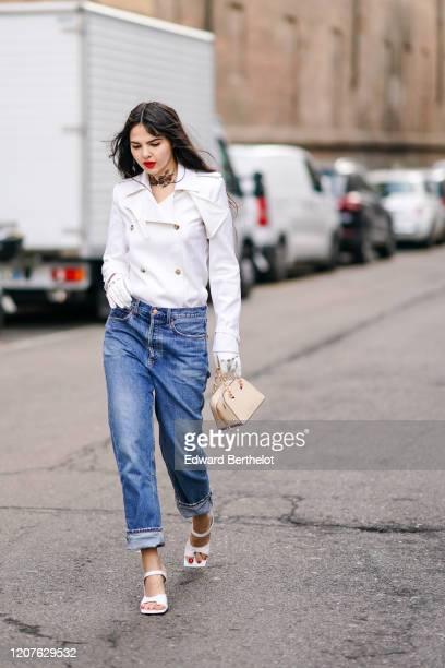 Doina Ciobanu wears a white double breasted jacket, gloves, blue cropped jeans, a bag, white shoes, outside Max Mara, during Milan Fashion Week...