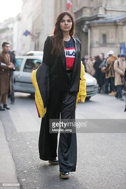 Doina Ciobanu wears an Are You Am I necklace Fila top yellow jacket off her shoulders Dior bag and a Roberta Einer AW16 'Shiny' suit pants after the...