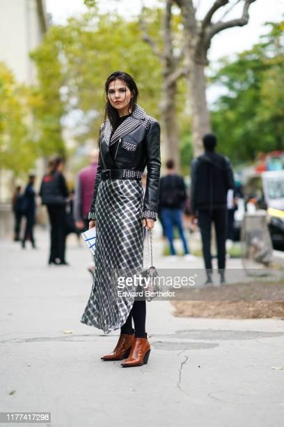 Doina Ciobanu wears earrings a studded black leather jacket a roses print metal mesh handbag a shiny black and silver checkered long skirt black...