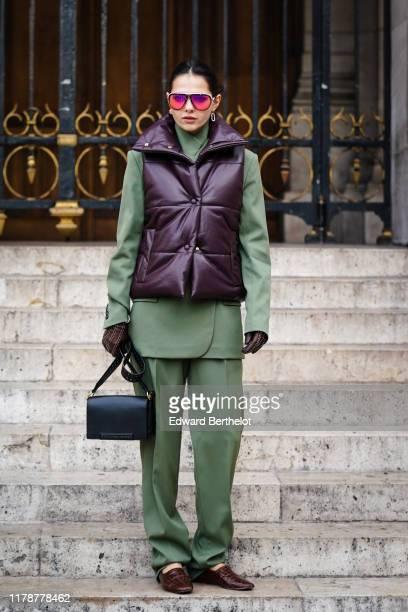 Doina Ciobanu wears earrings, sunglasses, an almond-green jacket, almond-green full-length pants, a dark brown puffer vest, dark brown gloves with...