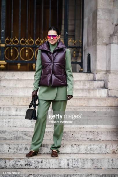 Doina Ciobanu wears earrings sunglasses an almondgreen jacket almondgreen fulllength pants a dark brown puffer vest dark brown gloves with apparent...