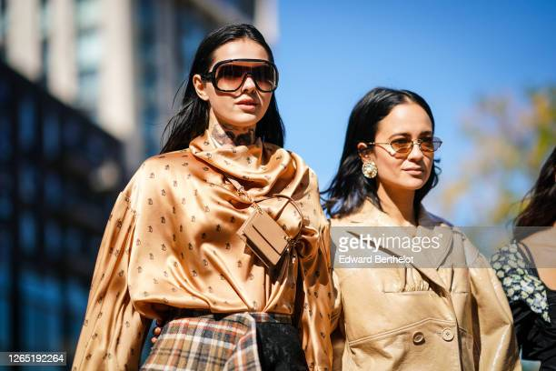 Doina Ciobanu wears sunglasses, a Burberry silky lustrous top, a small rectangular leather bag, during London Fashion Week September 2019 on...