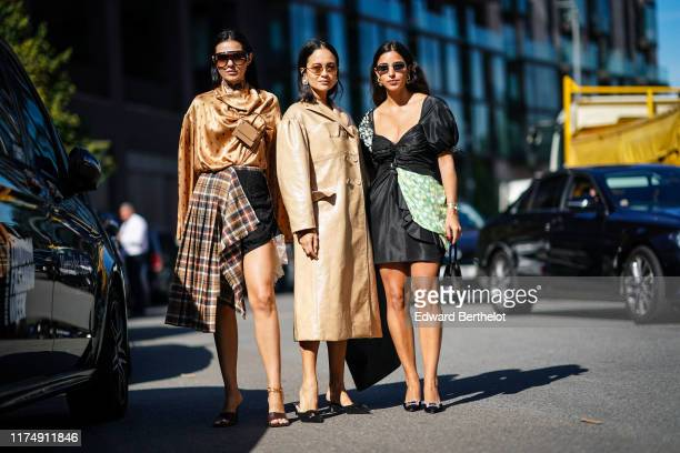 Doina Ciobanu wears sunglasses a golden shiny silky flowy top with printed features a brown mini bag attached to the top a tartan checked pattern...