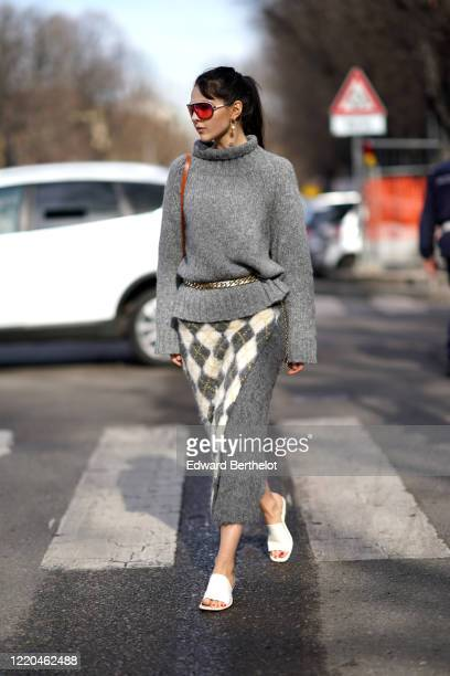 Doina Ciobanu wears sunglasses, earrings, a gray wool pullover, a belt, a gray wool skirt with argyle printed pattern, white sandals, outside Tod's,...