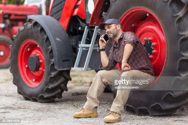 Das Geschäft auf dem Bauernhof Landwirt und Traktor