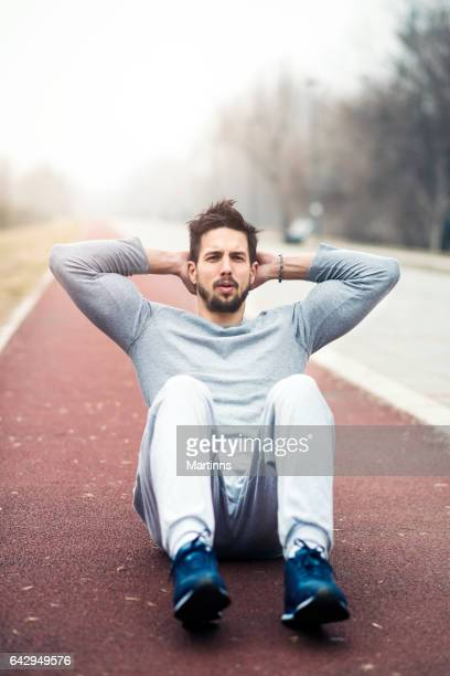 doing crunches outdoors - only young men stock pictures, royalty-free photos & images