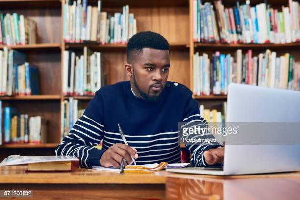 doing his research to get top marks - college student stock pictures, royalty-free photos & images