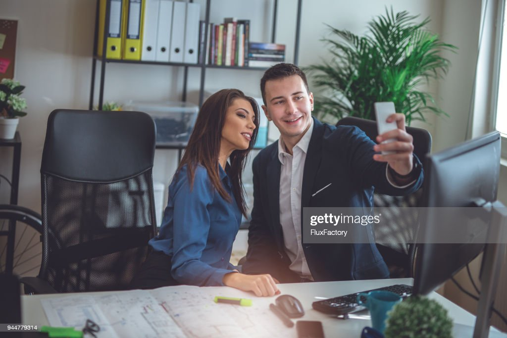 Doing selfies at the office while working : Stock Photo