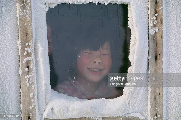 A Dolgan child presses her nose against the window of her home near the village of Syndassko Russia The Dolgans traditionally a nomadic people who...