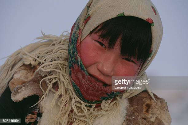 A Dolgan child welcomes a hunting party back to their camp near the village of Syndassko Russia The Dolgans traditionally a nomadic people who live...