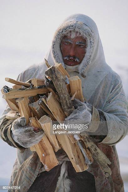 A Dolgan man carries firewood in his camp near the village of Syndassko Russia The Dolgans traditionally a nomadic people who live along the Taymyr...