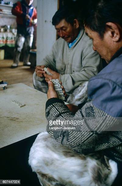 Dolgan men enjoy a game of dominoes in their home near the village of Syndassko Russia The Dolgans traditionally a nomadic people who live along the...