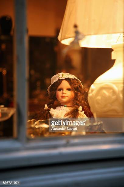 Doll and a lamp seen through window at dusk
