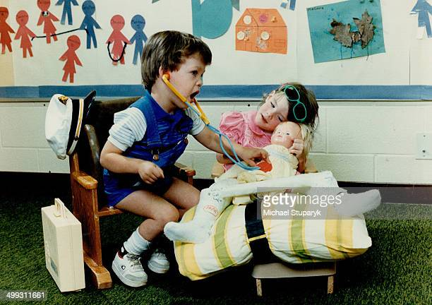 Doll doctor Eddie McGarry plays doctor with 3yearold Christie Ladner's doll baby at the Credit valley Treatment Centre for Children in Mississauga...