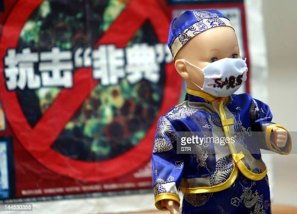 A doll donning a traditional Chinese costume and with the latest addition a mask to go with the SARS epidemic in Beijing 26 May 2003 on display in...