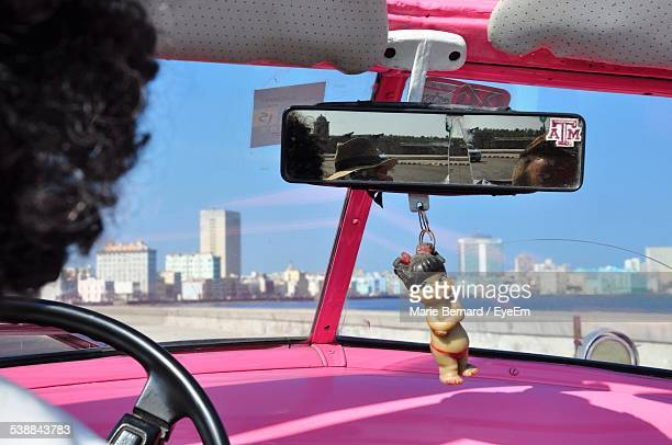 Doll In Chain Hanging On Rear-View Mirror In Car