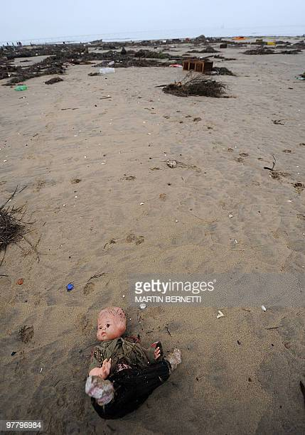 A doll is seen lying on the sand after a tsunami hit Penco 10 kms from Concepcion the day after a huge 88magnitude earthquake rocked Chile early...